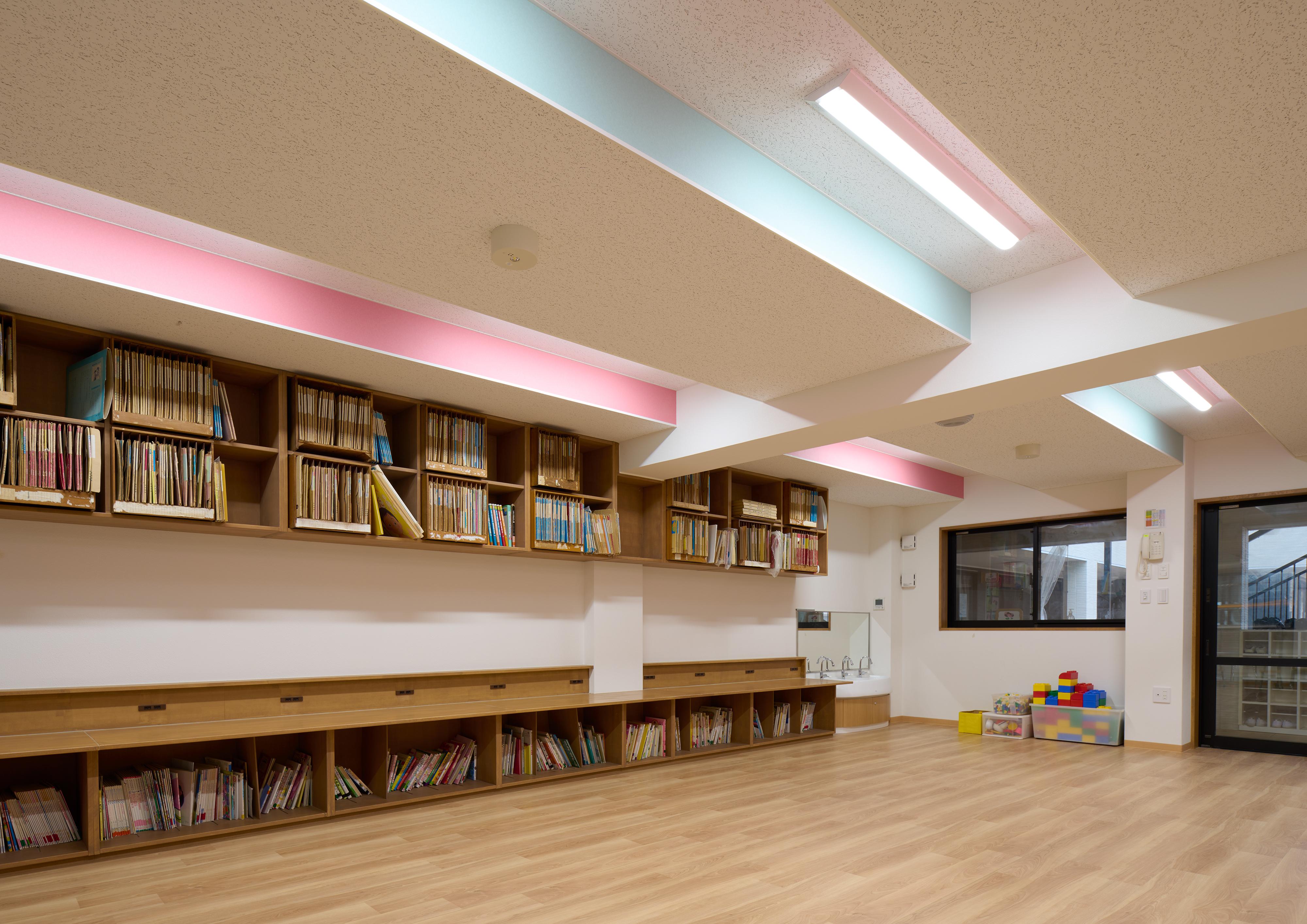 1階の視聴覚室や保育室等は石こうボードで覆った梁まわりと天井面に段差を設けて視覚的な広がり